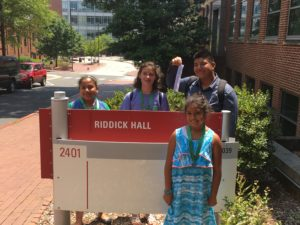 Youth posing by NC State's Riddick Hall sign.